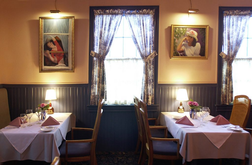 Photo of the Chez Nous dining room, with two tables on either side of a curtained window.