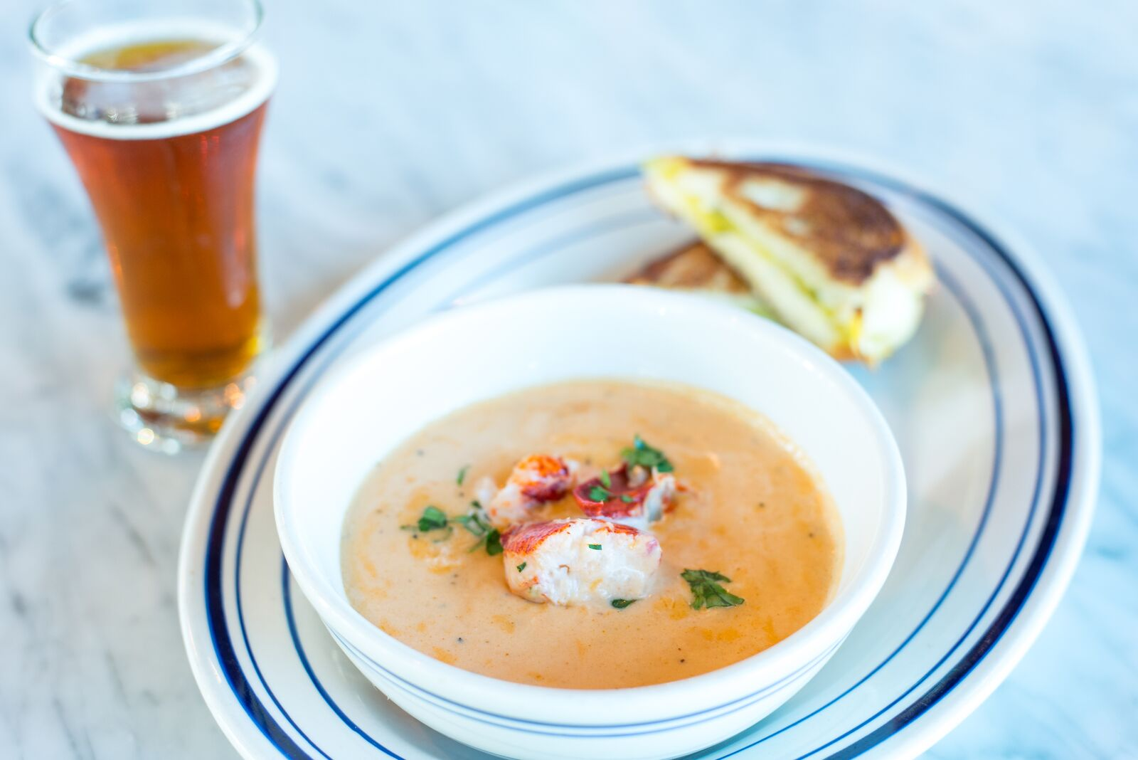 Photo of a bowl of lobster bisque, on a plate with a mini grilled cheese sandwich/