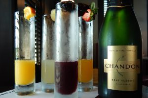 Photo of a bottle of Chandon Champagne and glesses of a mimona and blackberry, mango and ginger Champagne spritzers.