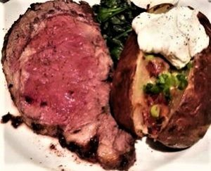 Photo of a piece of prime rib and a baked potato