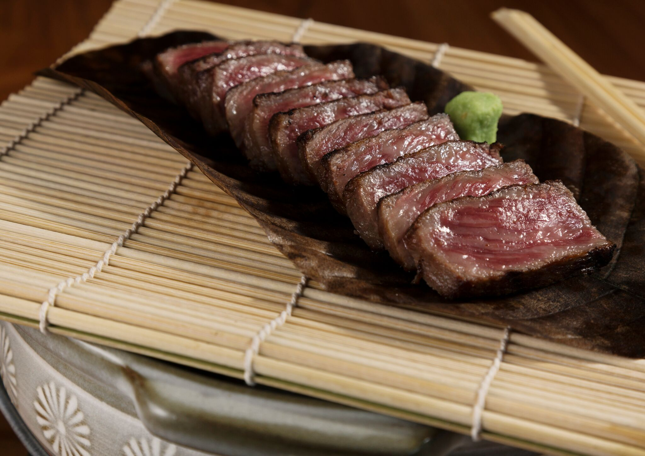 Photo of steak on a bamboo mat.
