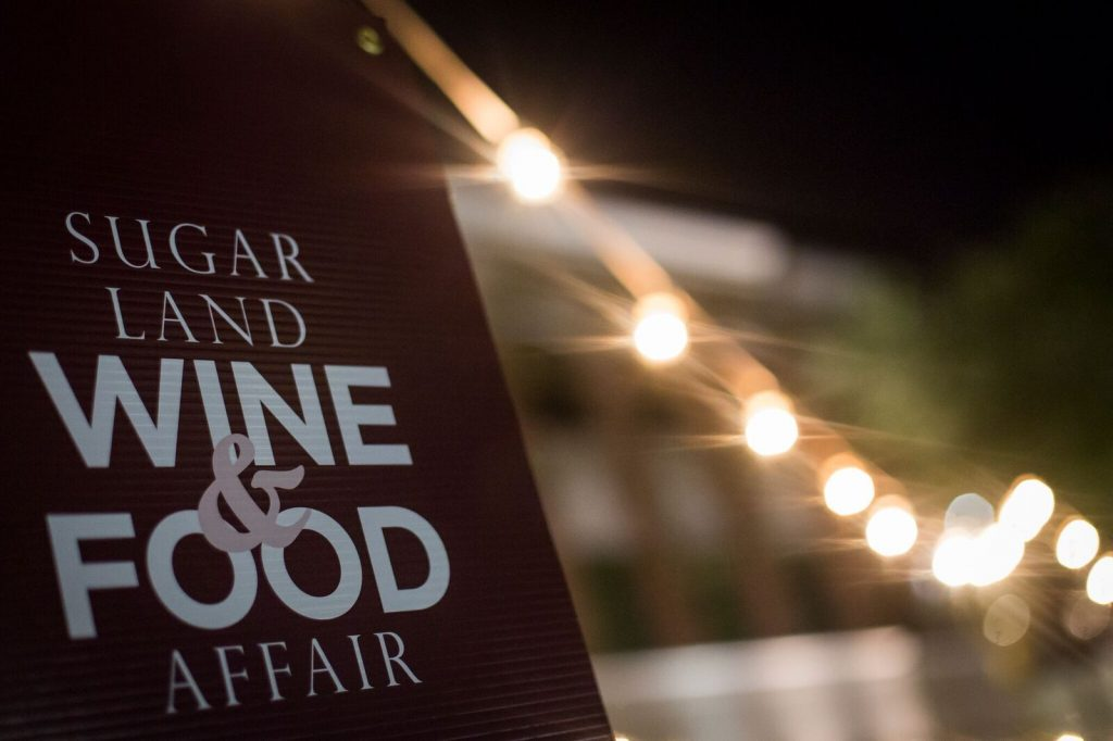 Photo of the Sugar Land Wine and Food Affair logo on an event board with lights in the background.