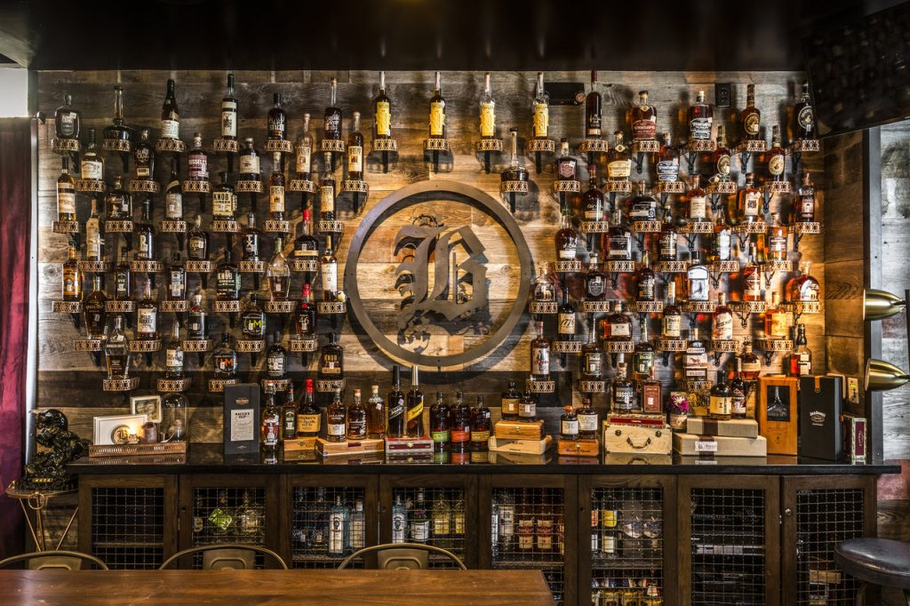Photo fo Bosscat Kitchen's Whiskey Wall with multiple bottles shown around Bosscat's B logo.
