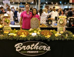 Picture of two employees standing behind a table decorated with produce.