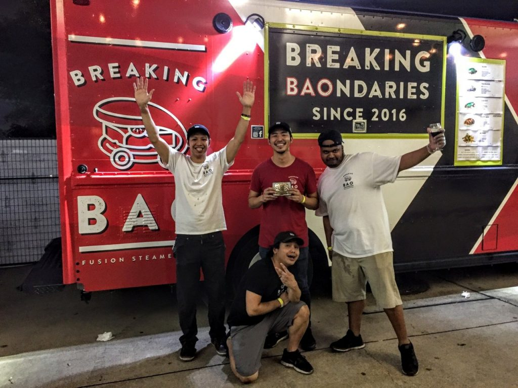 Picture of four guys posing in front of Breaking Bao food truck.