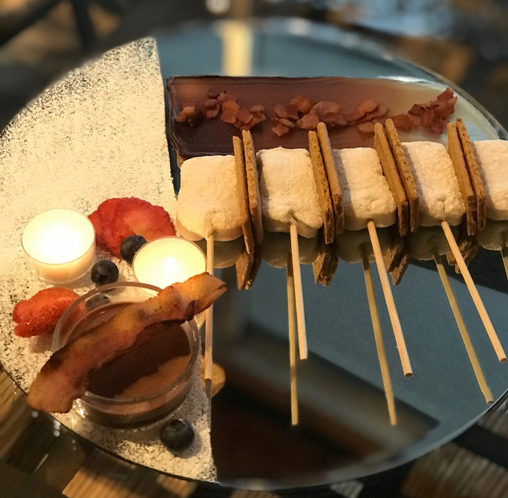 A plate of marshmallows, bacon and long sticks.