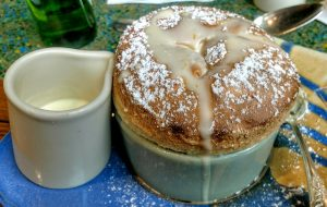 Photo of a Grand Marnier souffle with a little ceramic cup of cream next to it.