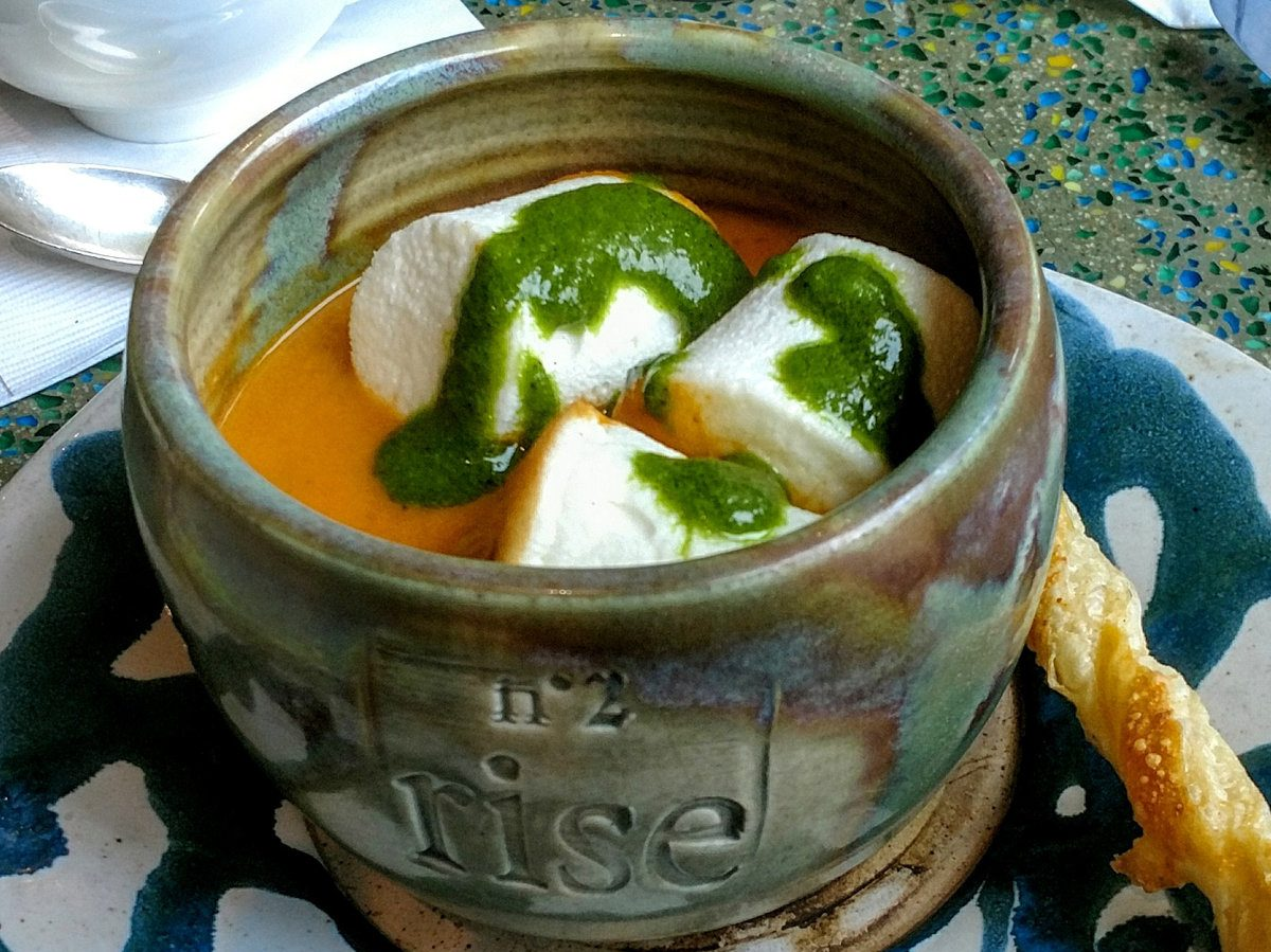 Picture of a crock pot of a tomato soup with cheese curds