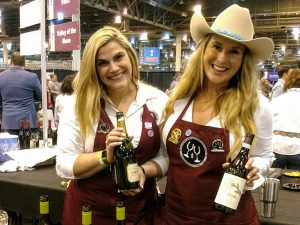 Picture of two women holding bottles of wine.