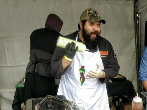 Photo of chef Donny Navarette holding a bottle of sauce.