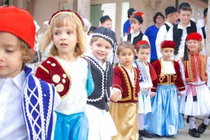 Picture of kids in traditional Greek dress dancing.