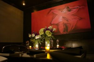 Picture of a table in Ambrosia's dining room in front of a red painting.
