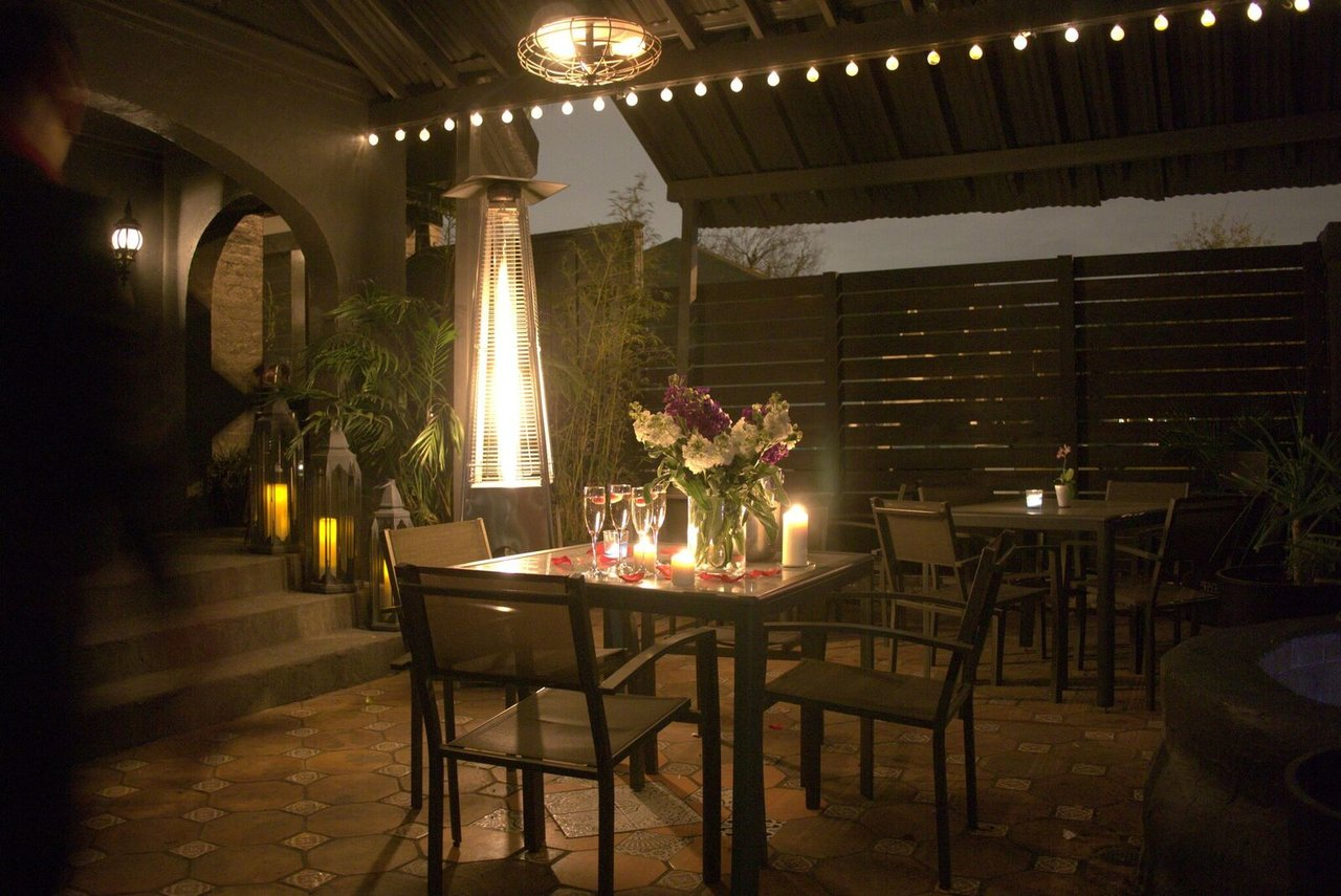 Picture of a tile courtyard with tables, tropical plants and soft lantern light.