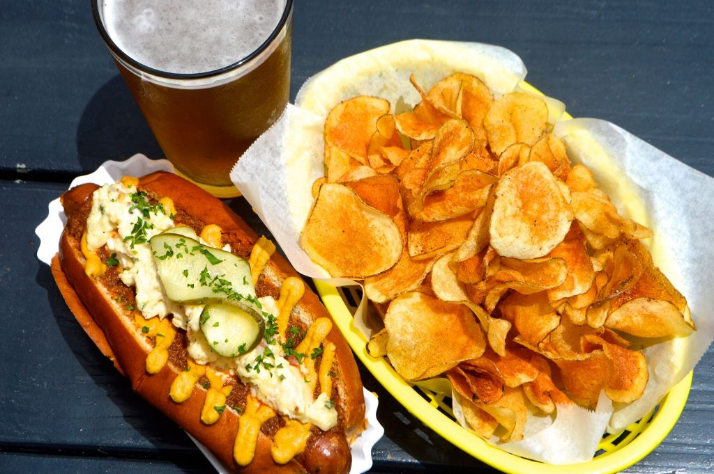 Overview of hot dog, chip and pint of beer