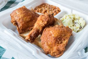 to-go order of fried chicken and sides at Gus's