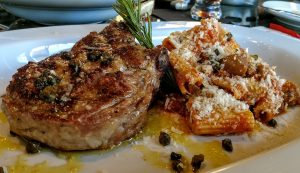 Picture of a veal cop on a plate with rigatoni pasta and capers