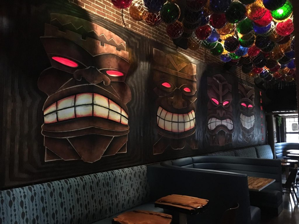 Photo of the interior at Kanaloa, with wooden tables, blue banquet and big tikis with toothy grins on the walls.