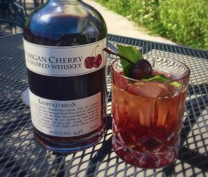 Picture of The Washington cocktail on a table with a bottle of cherry bourbon.