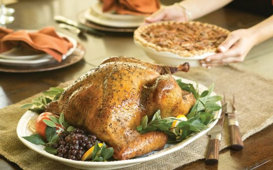 Photo of turkey on a platter on a table, surrounded by a pecan pie, green bean casserole and sweet potatoes.