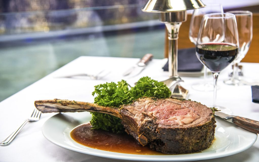 Picture of huge piece of prime rib on a plate.
