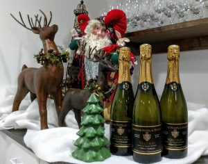 Picture of three bottles of sparkling wine against a Christmas tress and reindeer.