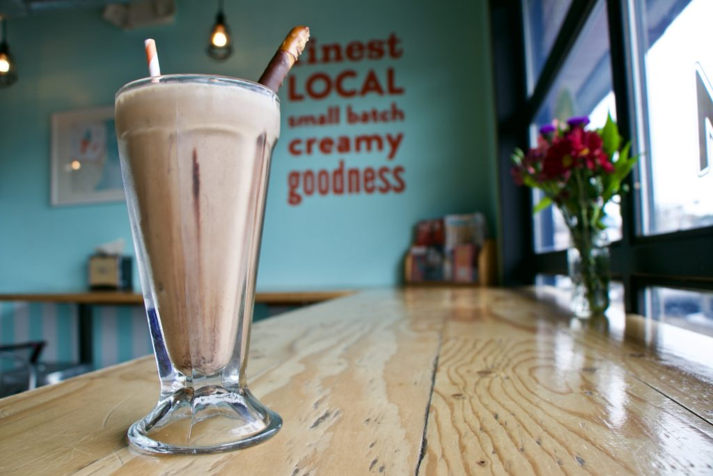 Image of a chocolate malt with a chocolate-covered pretzel stick in it sitting on a counter at Fat Cat Creamery.