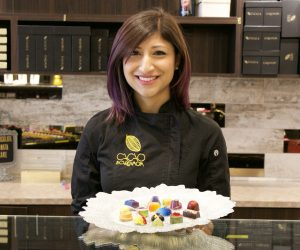 Photo of Annie Rupani holding a tray of fine chocolates