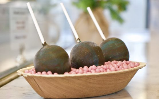 Picture of a dish of tiny pink sprinkle balls, topped with large cake balls on a stick.
