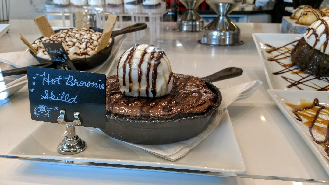 Photo of a large brownie taking up a whole pan, topped with vanilla gelato.