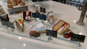 Picture of a bakery case with several cake slices in it.