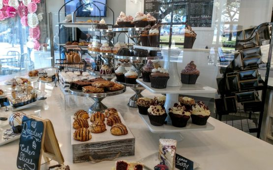 Picture of a pastry case with cakes, brownies, cupcakes and other sweets.