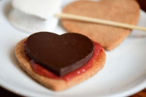 Picture of a heart shaped graham cracker with a heart shaped piece of chocolate on top.