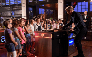 Children standing in front of demo with chef Gordon Ramsay in a cooking studio.