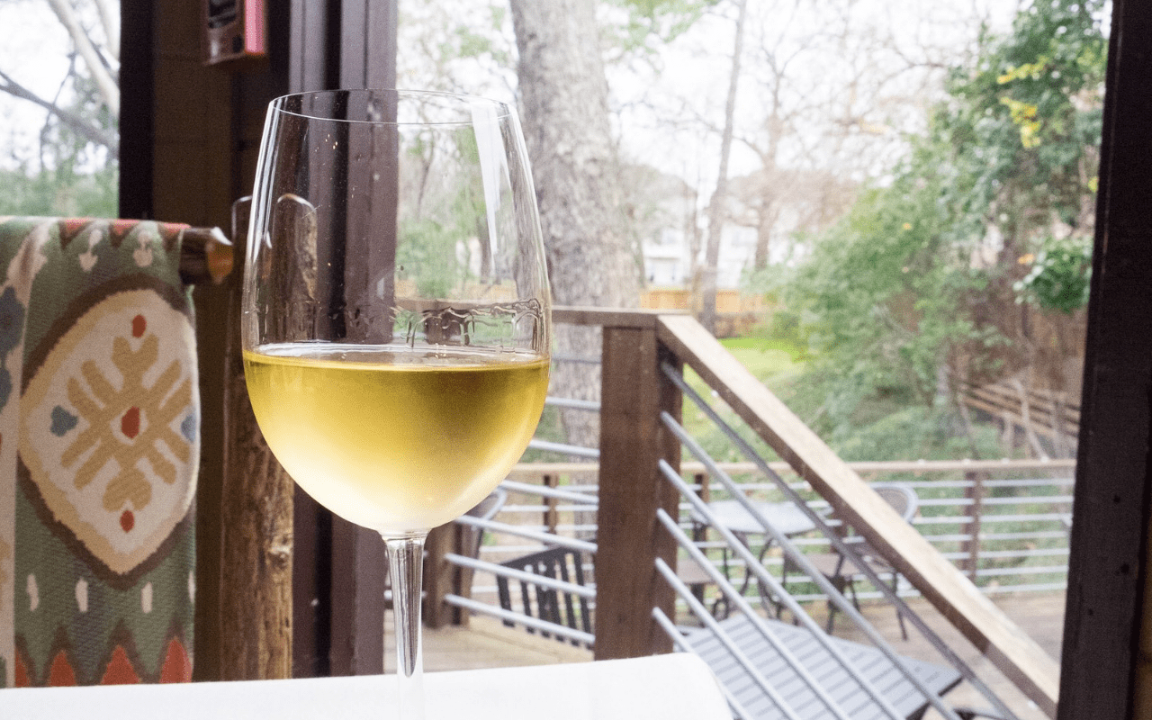 Glass of white wine with porch and nature view