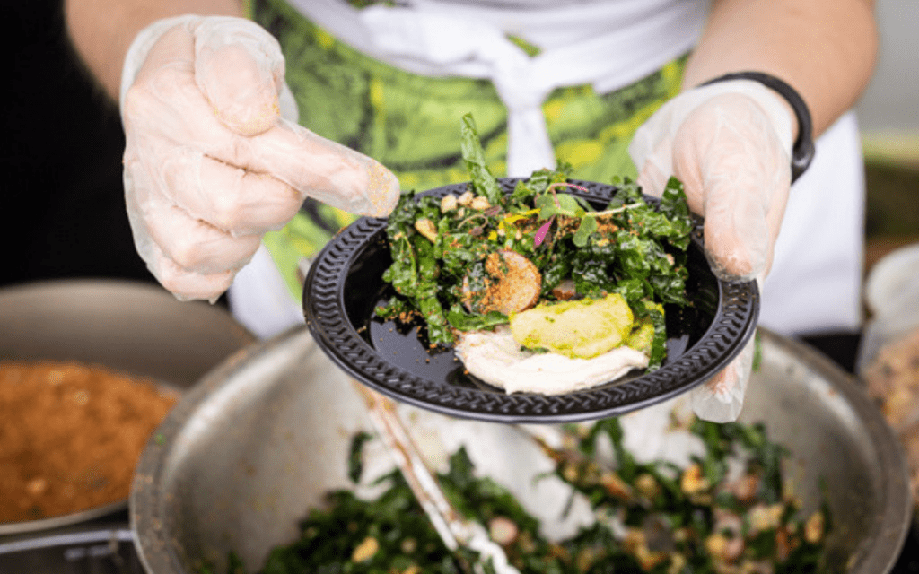 Person holding a plate of salad over a bowl of salad
