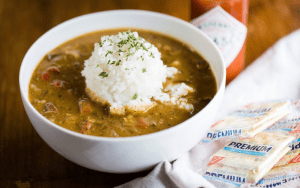 Close-up of bowl of gumbo topped with a scoop of white rice