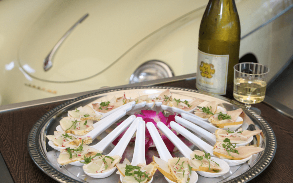 Round tray of small bites on spoons, bottle of white wine, and part of a cream colored antique car in background