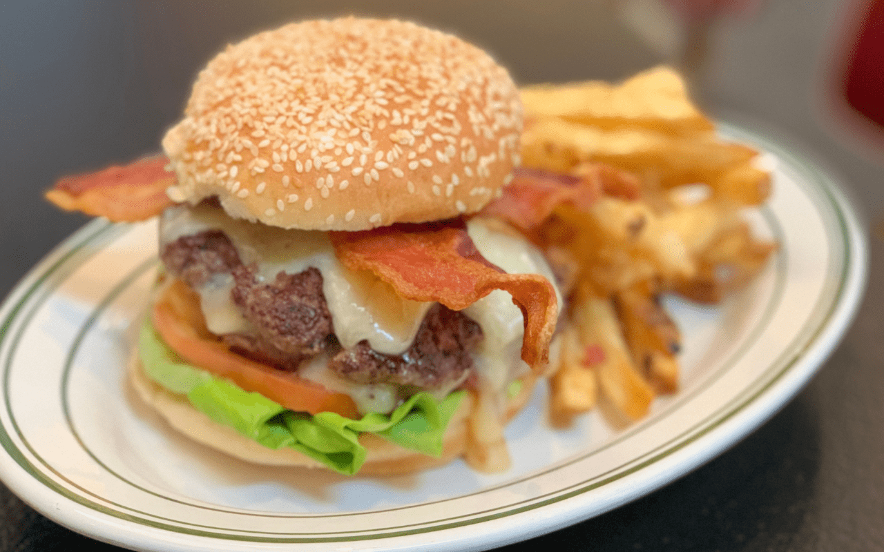 Close-up of a larger double-patty hamburger with cheese and bacon plus fries in background