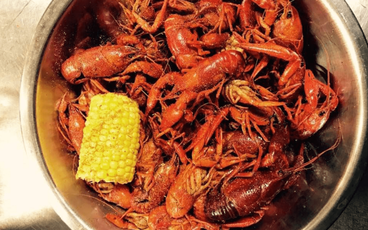 Metal bowl filled with cooked crawfish and a half-ear of corn.
