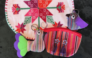 Assorted small Mexican crafts including birds, earrings and a bag in pinks, purples and reds