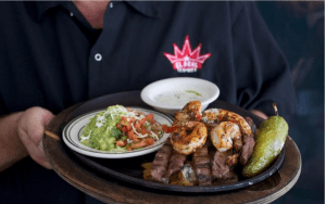Platter of beef fajitas with side of guacamole, pico and sauce.