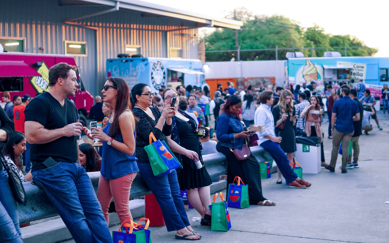 Groups of people standing and talking with food trucks in background
