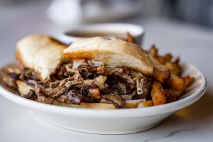 Picture of an overflowing beef sandwich on a plate with mushrooms and au jus.