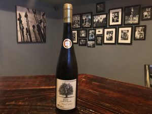 Picture of a bottle of wine on a table in front of a wall full of photos.