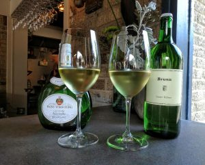 Picture of two bottles of wine with glasses of wine in front of them on a bar.