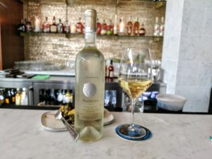 Picture of a bottle of wine on a bar top, next to a wine of wine and in front of a dish of spanakopita