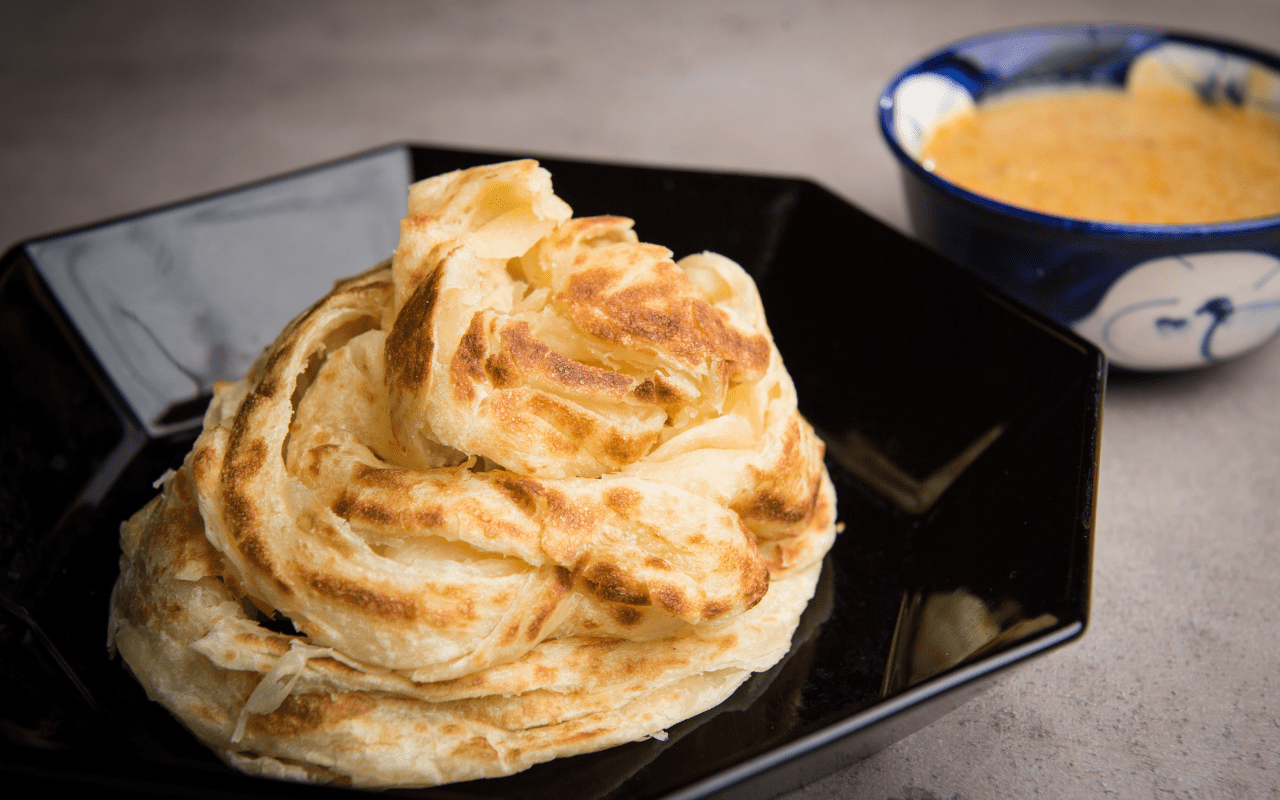 Roti canai on black plate with sauce