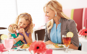 Young child and mother at a table with food and drink
