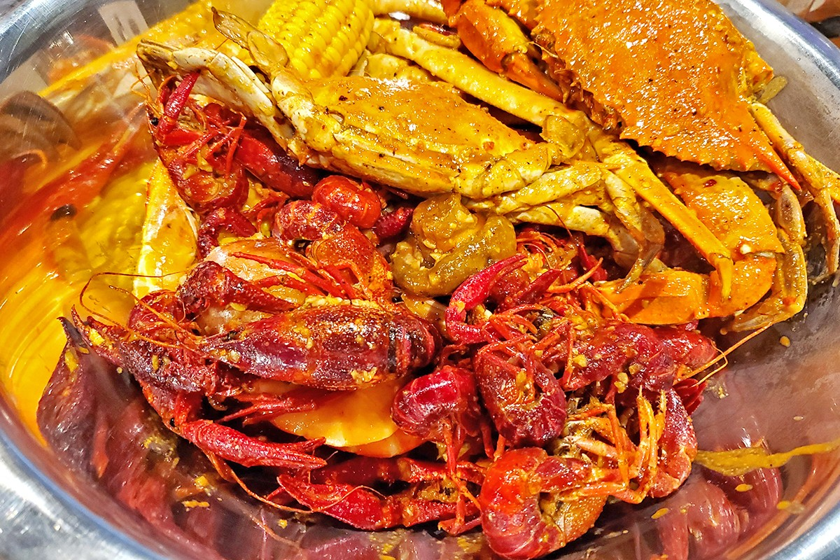 Crawfish, crabs and corn tossed in the house sauce at Yummy Crawfish & Seafood