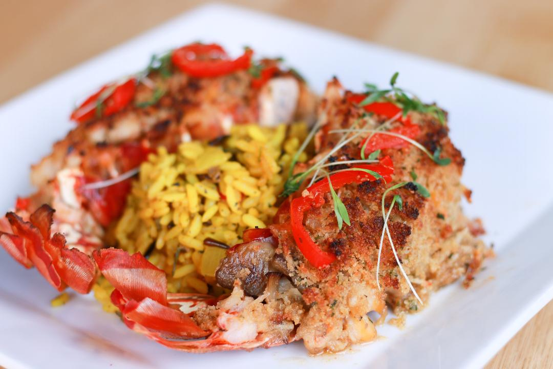 Photo of lobster tails atop yellow rice on a plate
